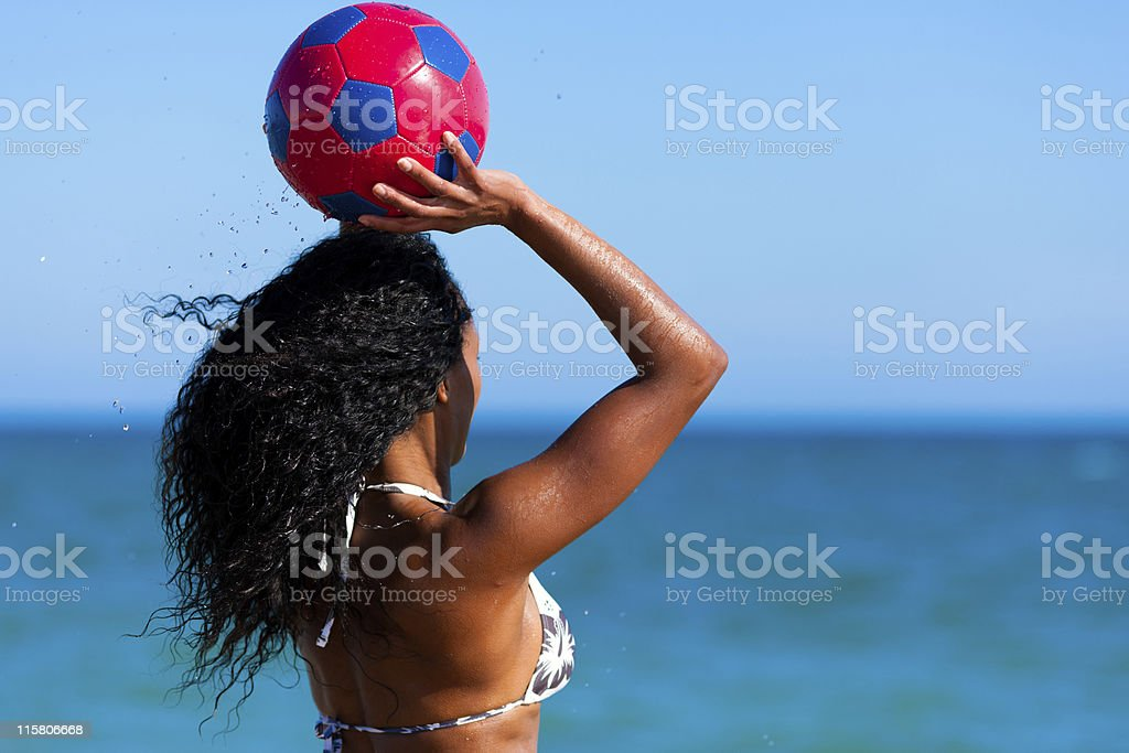 Woman at the beach playing soccer stock photo