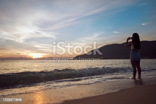 928866530 istock photo Woman at the beach taking pictures 1203371849