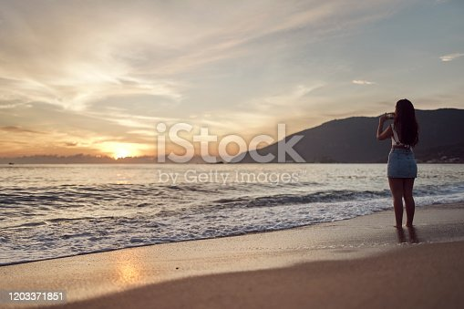 928866530 istock photo Woman at the beach taking pictures 1203371851