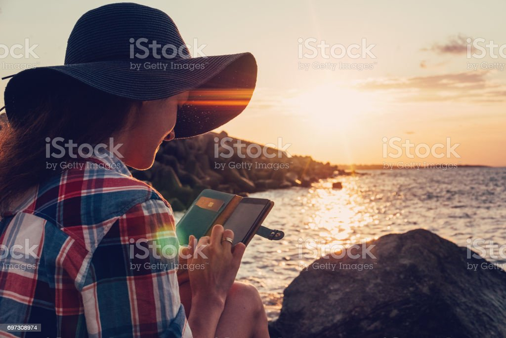 Woman at the beach texting on sunset stock photo
