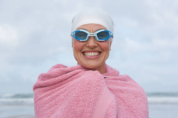 woman at the beach wrapped in a towel  swimming goggles stock pictures, royalty-free photos & images