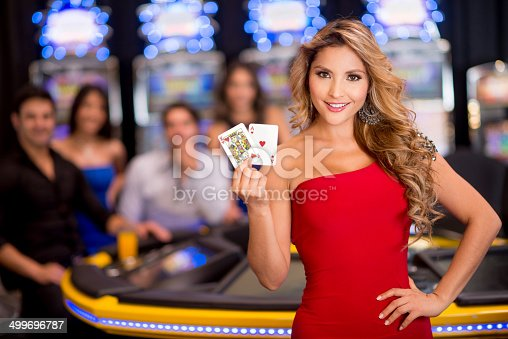 Happy woman at the casino playing cards (Note: Card design is our own)