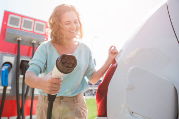A woman at the charging station for electric vehicles A woman stands at the charging station and holds a plug of the charger for an electric car alternative fuel vehicle stock pictures, royalty-free photos & images