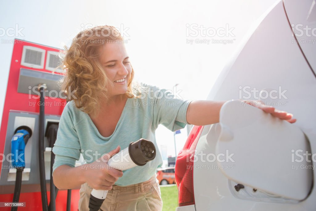 Una mujer en la estación de carga para vehículos eléctricos - Foto de stock de Adulto libre de derechos