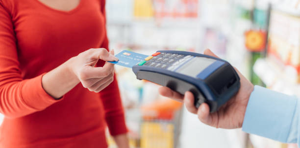 Woman at the checkout Woman at the supermarket checkout, she is inserting her credit card in the terminal, shopping and retail concept credit card purchase stock pictures, royalty-free photos & images
