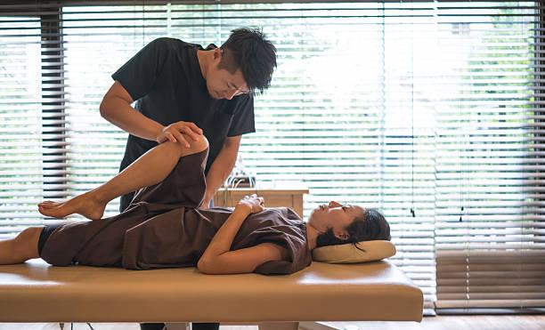 woman at the chiropractor - chiropraktik wellness stock-fotos und bilder