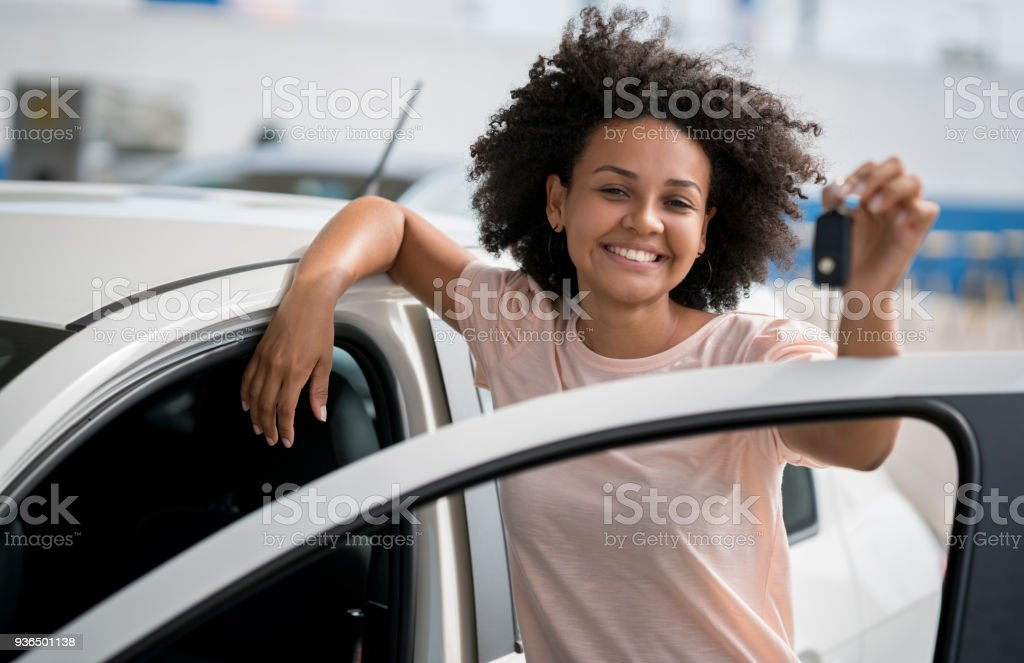 Woman at the dealership holding keys to her new car stock photo