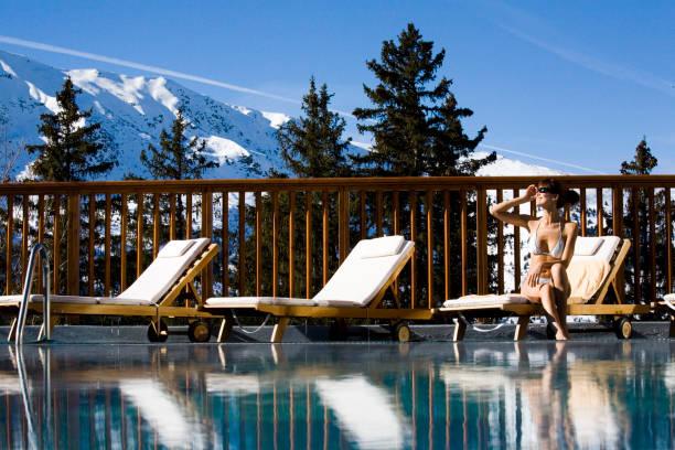 frau am rande des einen außenpool in den schneebedeckten bergen - hotel in den bergen stock-fotos und bilder