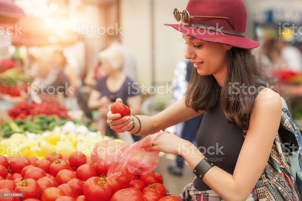 Woman at the fruit and vegetable market stock photo