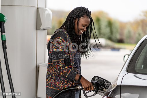 Woman at the gas station refueling car