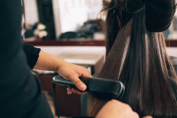 femme à la coiffure, obtenant ses cheveux coiffés - coiffure africaine photos et images de collection