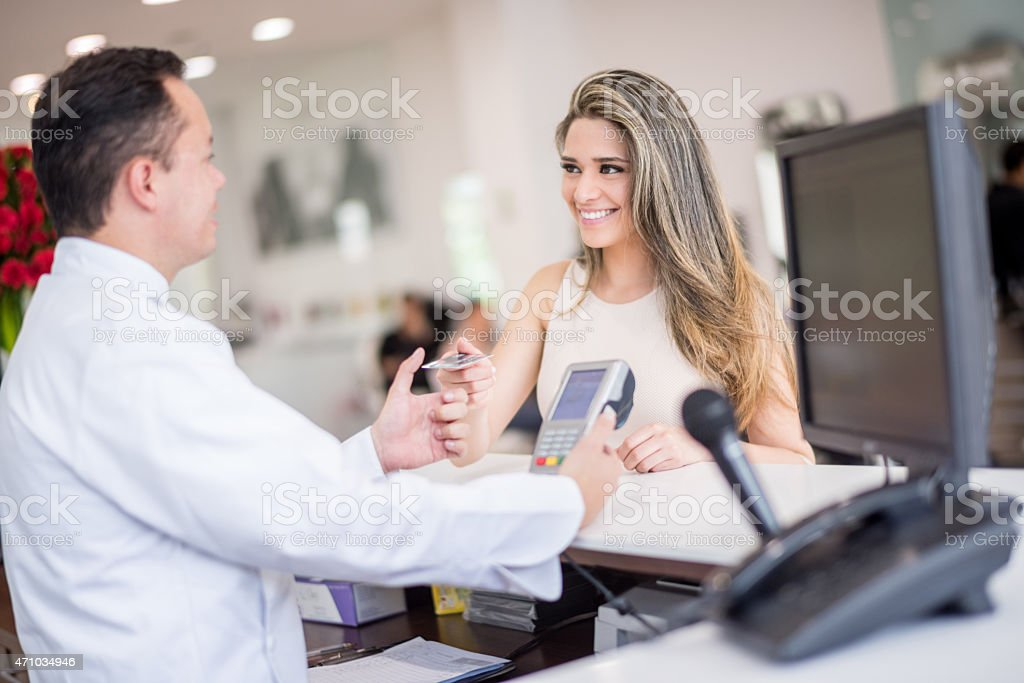 Woman at the hair salon paying by card stock photo