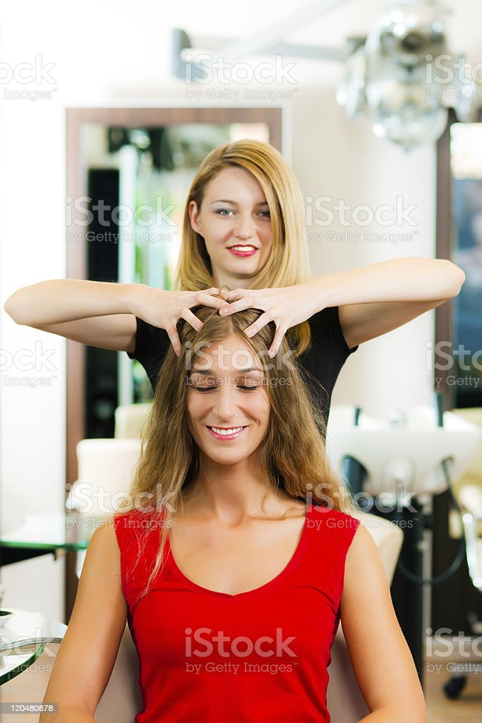 Woman at the hairdresser getting a head massage royalty-free stock photo