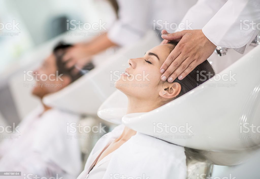 Woman at the hairdresser washing her hair stock photo