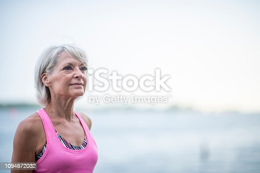 A Caucasian senior woman is standing next to a lake, and gazing into the distance.