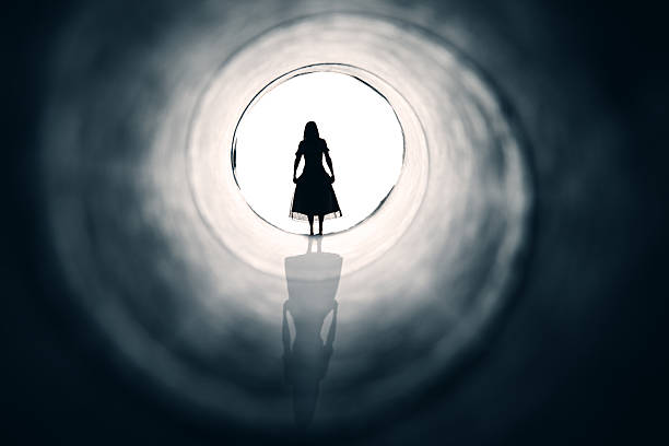 Woman At The Light End Of Tunnel stock photo