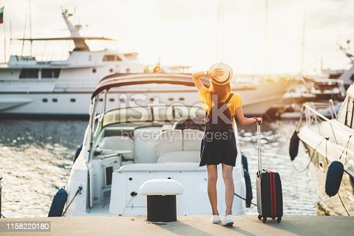 Rear view of tourist woman staring at the yachts before boarding