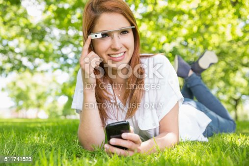 Cork, Ireland - June 5, 2014: Woman at the park smiling and using google glass and a mobile phone