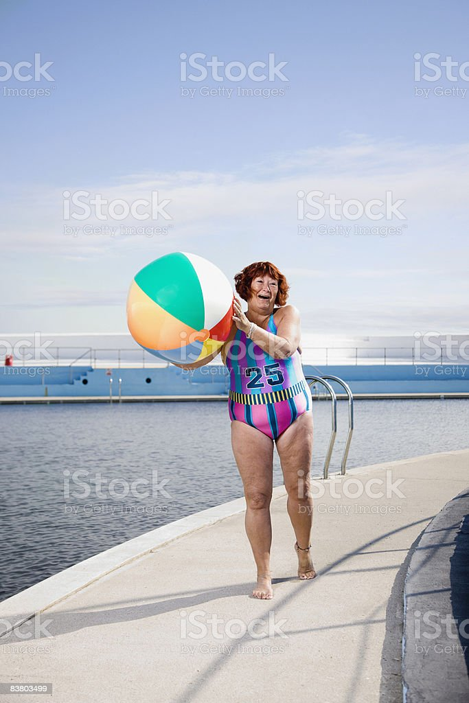 Woman at the side of a pool with a beach ball   photo libre de droits