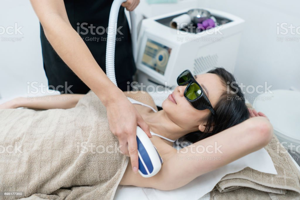 Woman at the spa getting laser hair removal stock photo