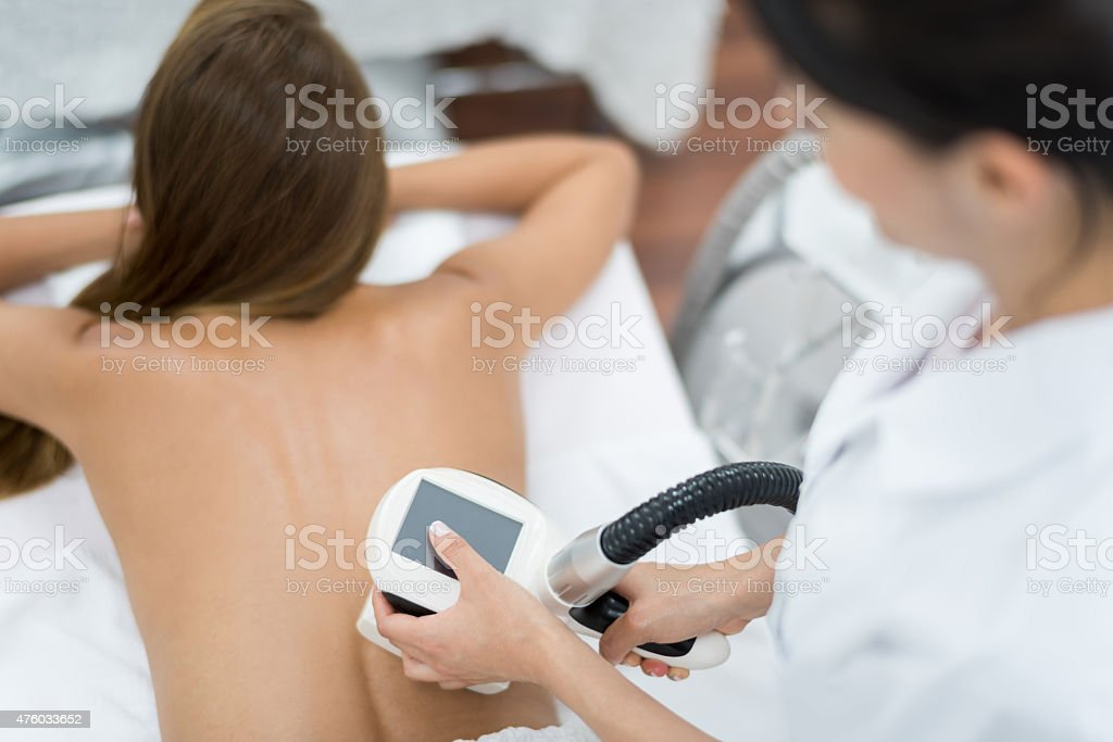Woman at the spa getting laser therapy stock photo