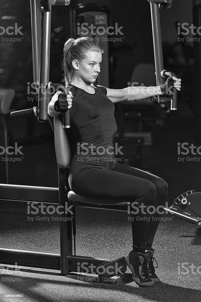 Woman at the sport gym doing arms exercises on a royalty-free stock photo
