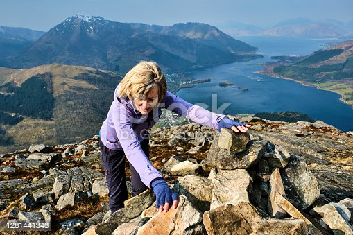 istock Woman at the summit of the Pap of Glencoe, Scotland 1281441348