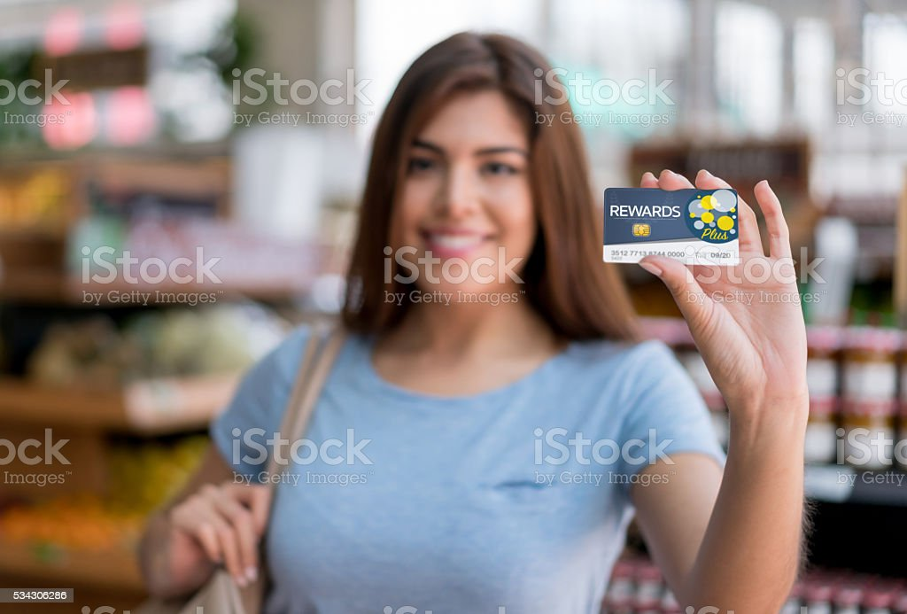 Woman at the supermarket holding a rewards card stock photo