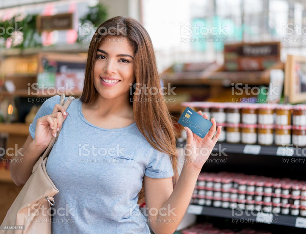 Woman at the supermarket paying by card stock photo