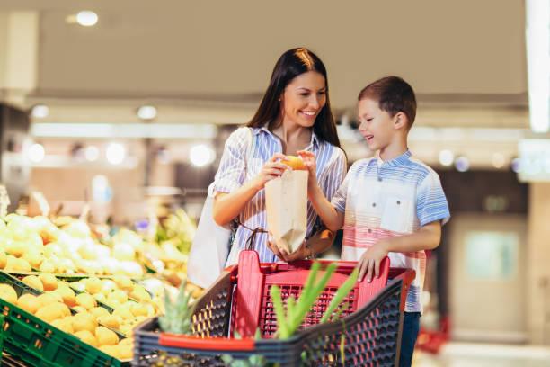 Mujer en el supermercado con su hijo comprando comestibles - foto de stock