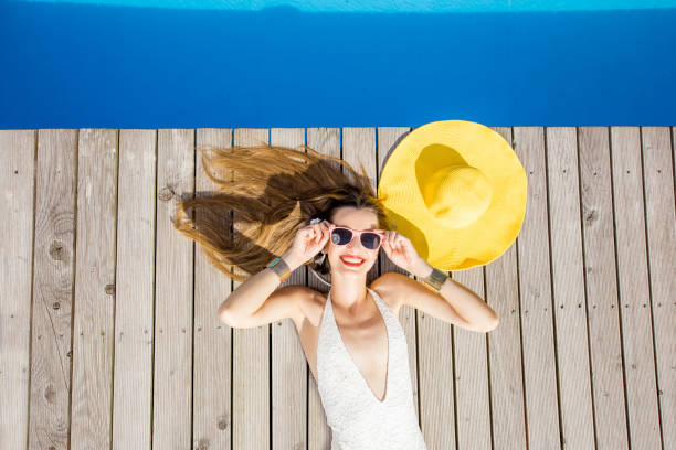 Woman at the swimming pool Playful woman lying with yellow sunhat on the poolside. Summer vacation concept sunbathing stock pictures, royalty-free photos & images