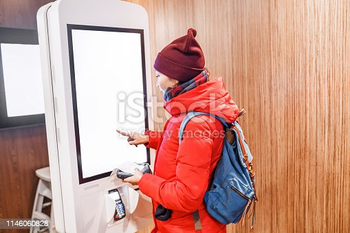 A woman at the touch screen payment terminal