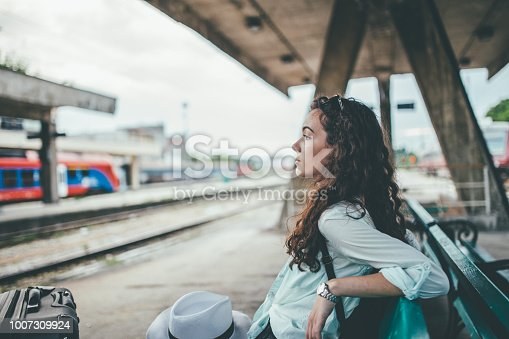 Young woman waiting for the train at the train station