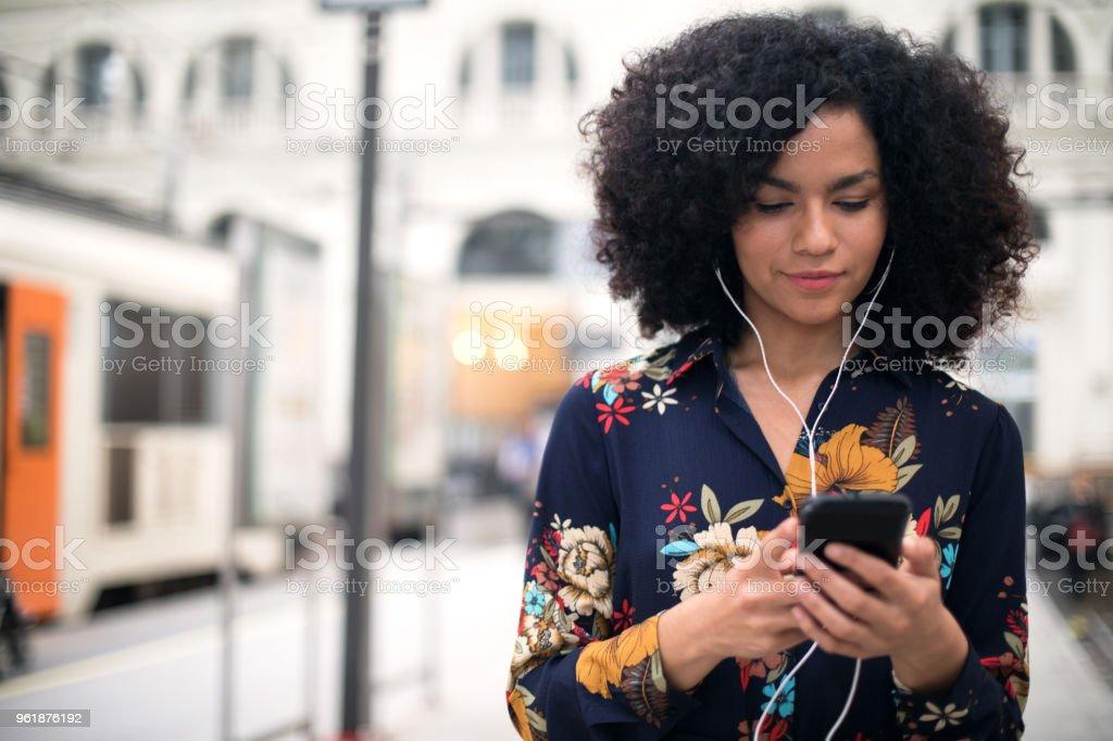 Vrouw op het station met behulp van de mobiele telefoon. - Royalty-free 20-29 jaar Stockfoto