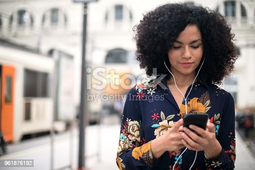 istock Woman at the train station using mobile phone. 961876192