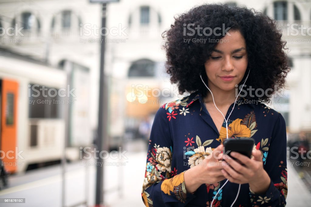 Woman at the train station using mobile phone. stock photo