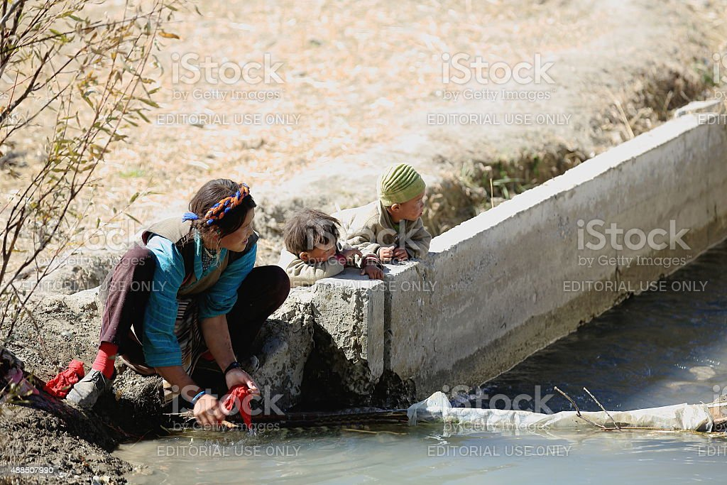 Woman at wash with two kids. Gepelwater Mill area-Tibet. 1661 stock photo