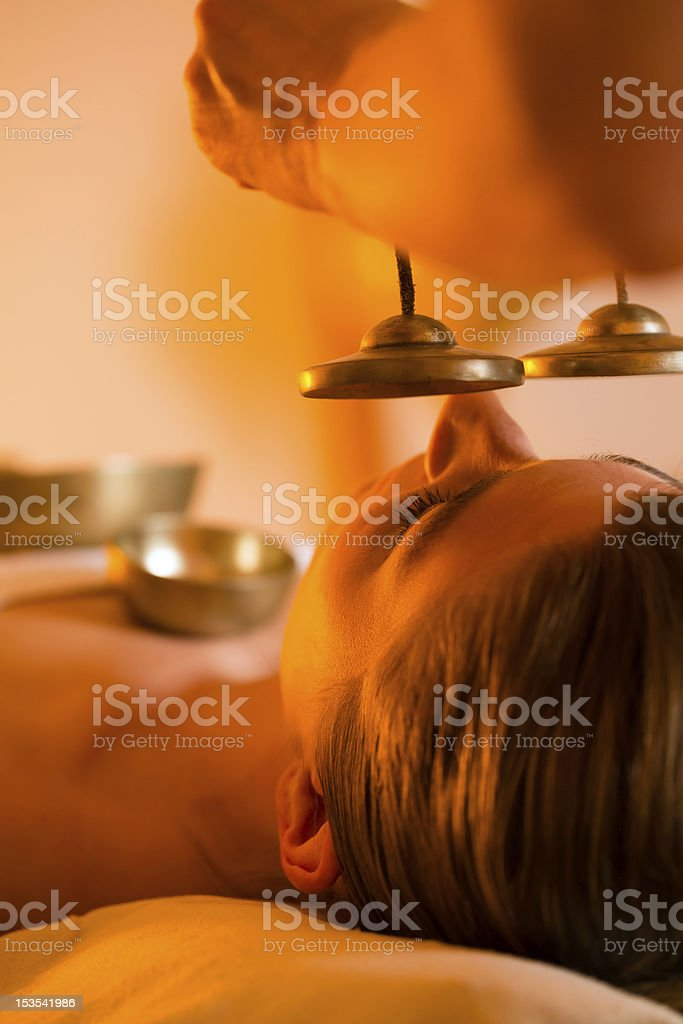 Woman at Wellness massage with singing bowls royalty-free stock photo