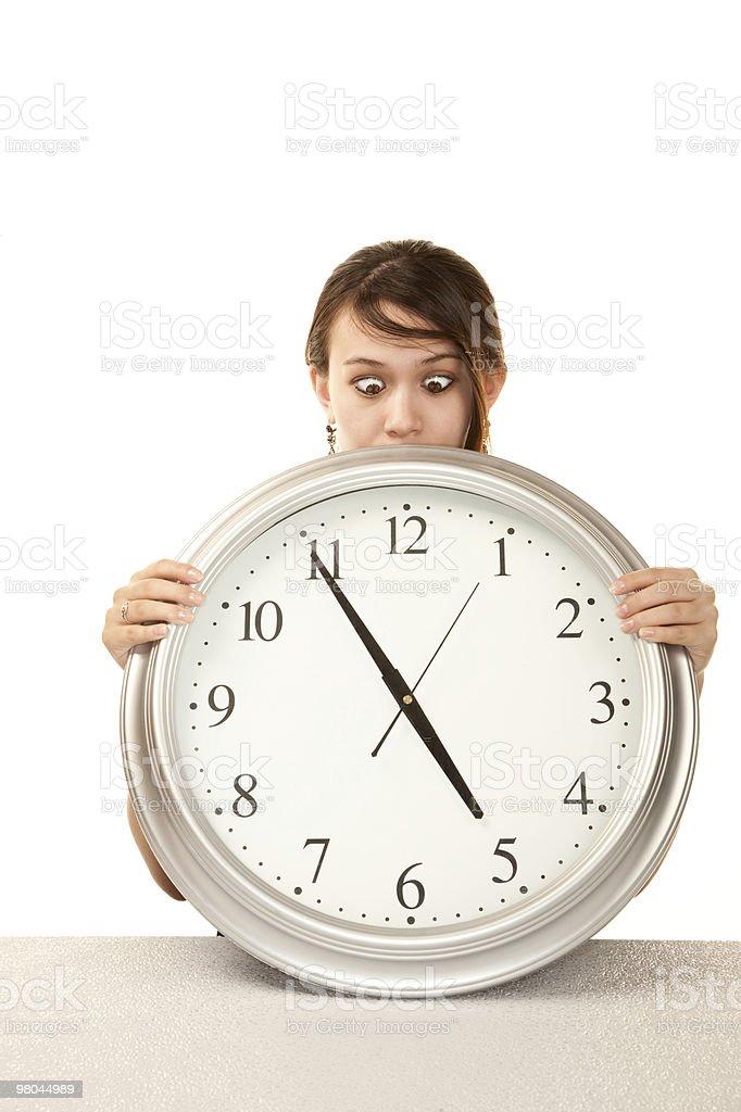 Donna in ufficio con grande orologio foto stock royalty-free