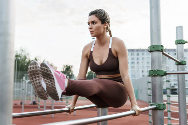 Woman athlete during calisthenics workout on a parallel bars stock photo