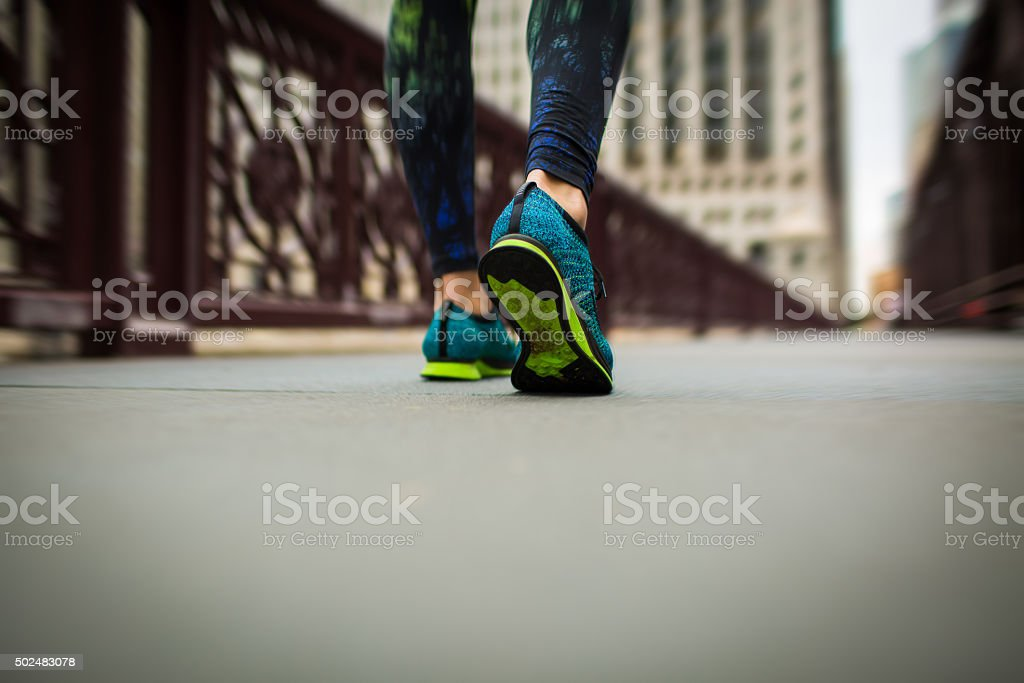 woman athlete feet and shoes while running stock photo
