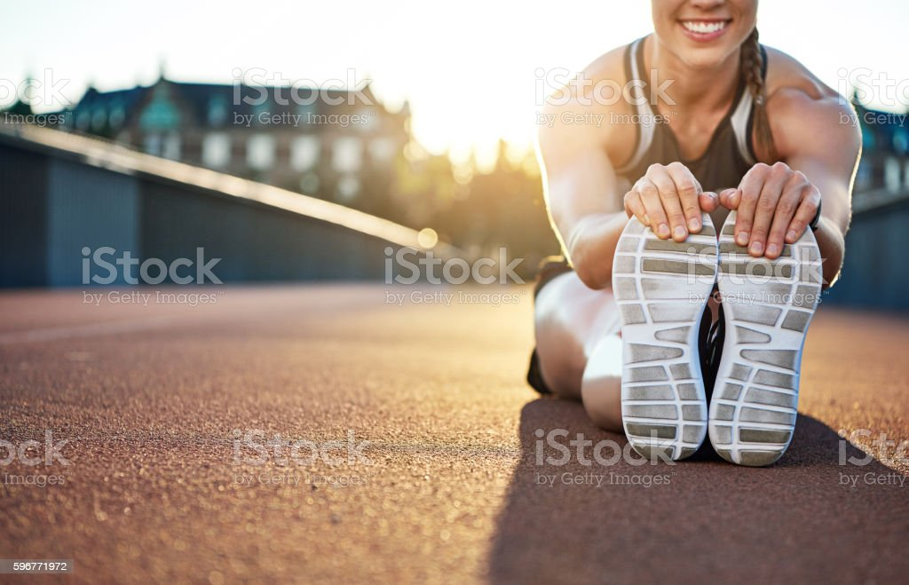 Woman athlete grabs her shoes as she stretches stock photo