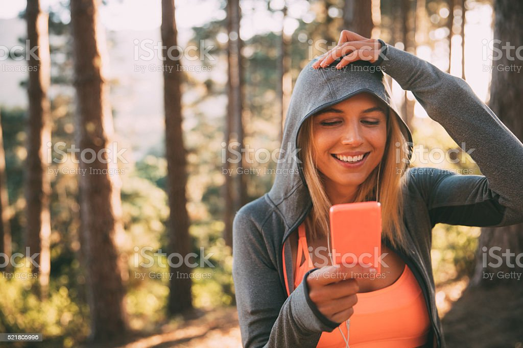 Woman athlete in exercise hoodie taking a selfie in nature stock photo
