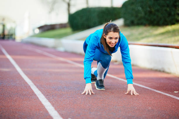 Woman athlete in starting position for running outdoors stock photo