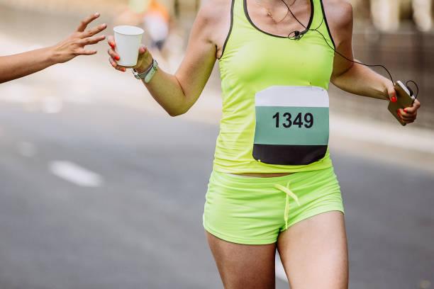 corredor atleta mujer correr con taza de agua - foto de stock