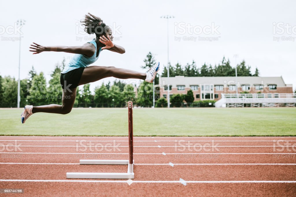 Woman Athlete Runs Hurdles for Track and Field - Zbiór zdjęć royalty-free (Afroamerykanin)