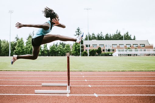 A young woman does hurdling training for her track competition training.  Captured mid- jump. Horizontal image with copy space.