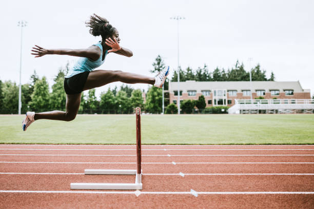 woman athlete runs hurdles for track and field - athlete stock photos and pictures