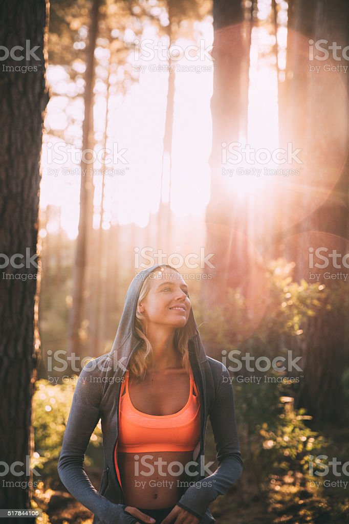 Woman athlete smiling in a forest with morning sunflare stock photo