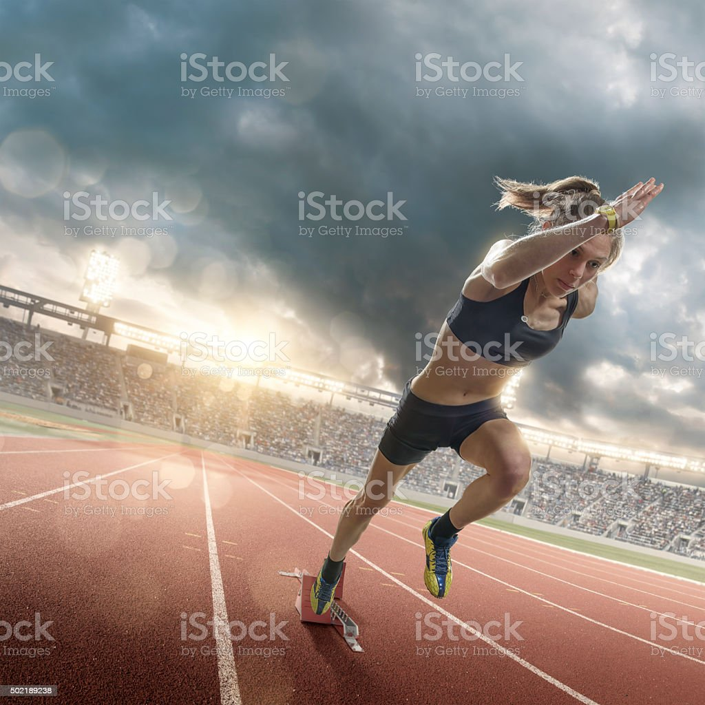 Woman Athlete Sprinting From Blocks on Running Track in Stadium stock photo